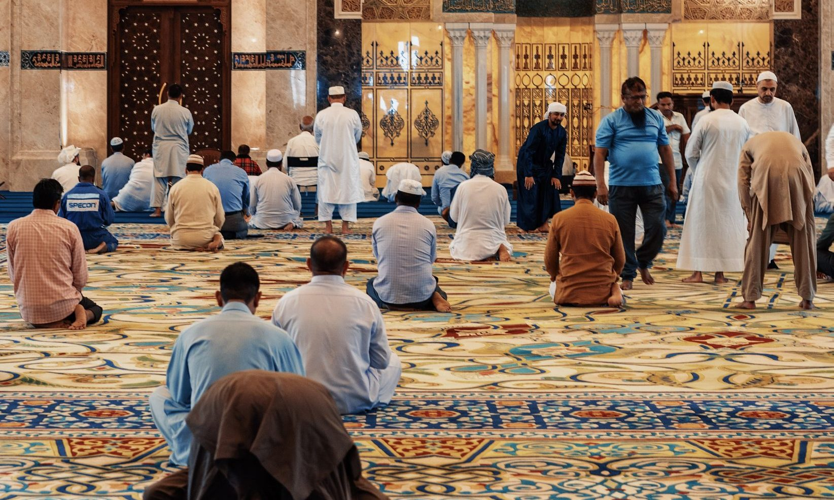 men kneeling and bowing inside building
