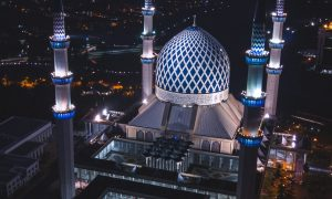white and blue dome concrete building with 4-towers during night time
