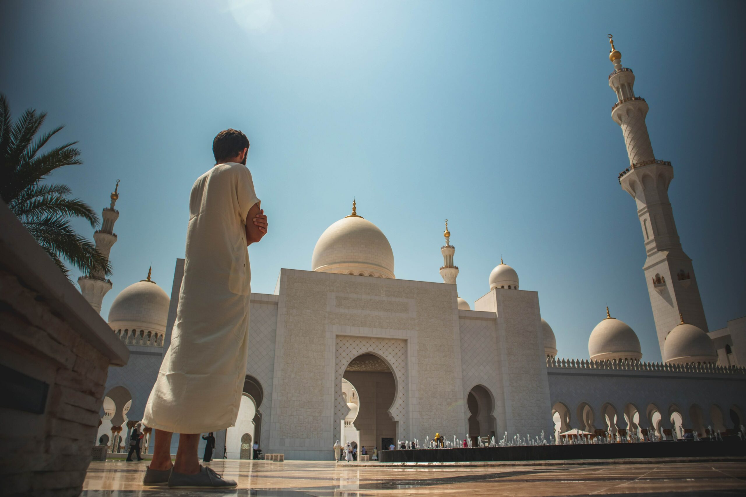 man standing near white mosque