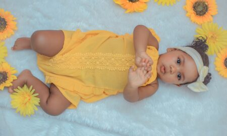 baby in yellow dress lying on white textile