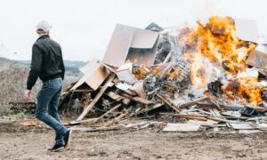 man in black jacket and blue denim jeans standing in front of bonfire