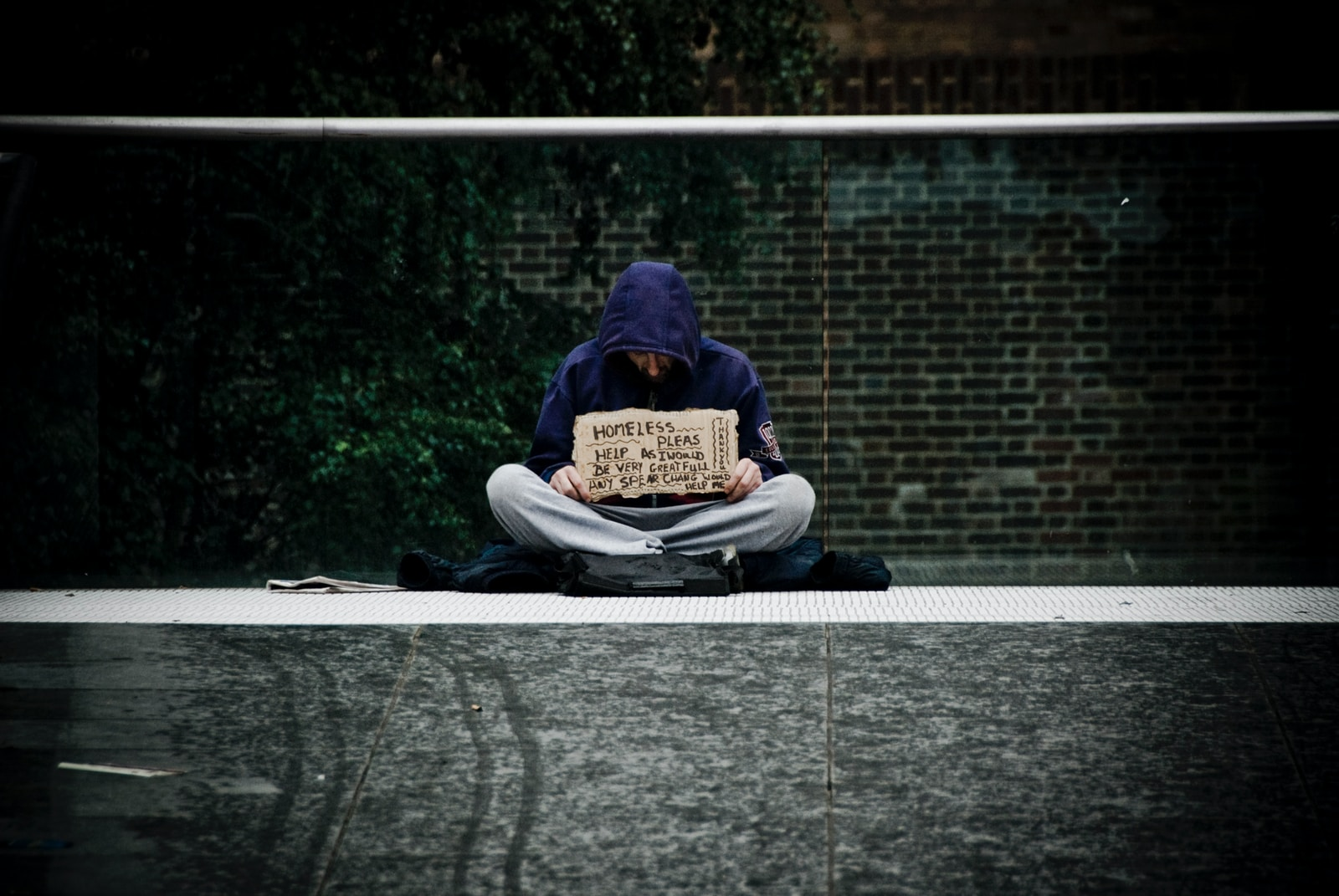 man in blue hoodie reading book on gray concrete road during daytime