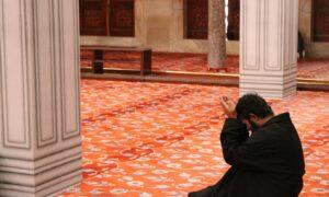 man in black robe sitting on red floor