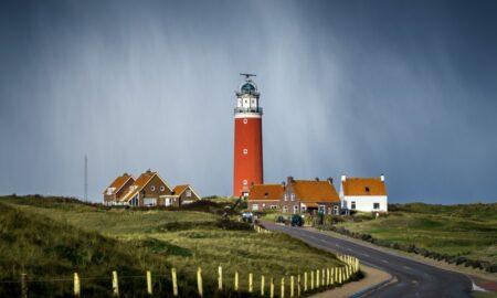 asphalt road between grass field going to brown lighthouse beside houses under cloudy sky
