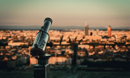 selective focus photography of telescope by cityscape during daytime